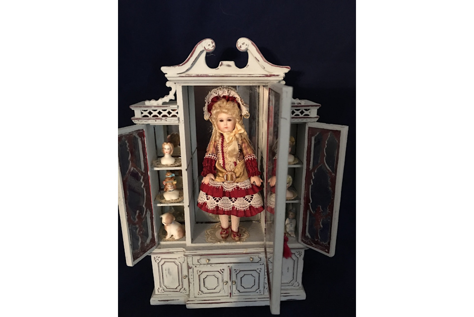 doll and heads in cabinet