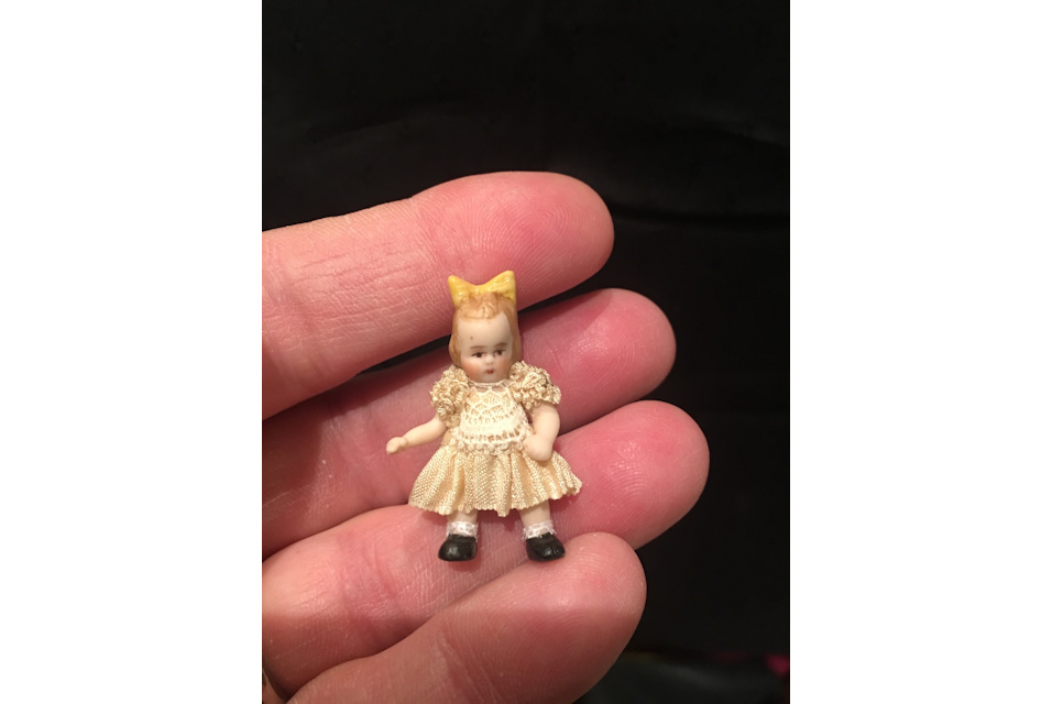 doll in hand yellow bow